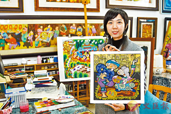 ■農民版畫師黃袁媛展示她創作的綦江農民版畫作品。