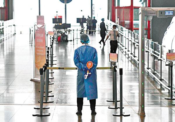 ■三類人員禁止離京。圖為一名工作人員昨日在北京某機場等待為乘客測溫。 法新社