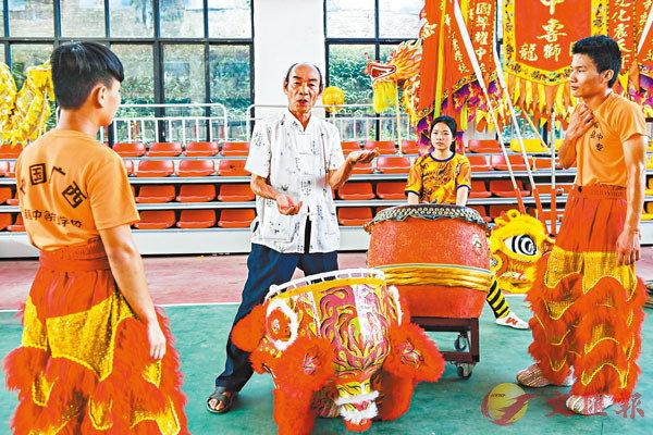 ■藤縣獅舞傳承人鄧明華(左二)給邱海威(左一)和黃慶良(右一)講解舞獅技巧。