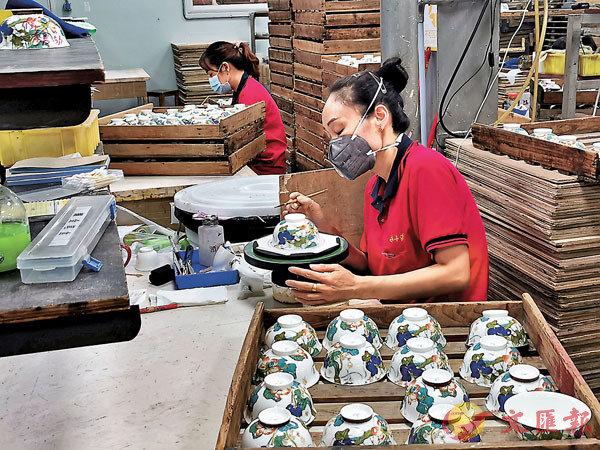 ■為了保住企業2,000多個員工,國瓷永豐源針對國內中端消費者推出「幸福禮」。圖為工人們正在趕製中餐具。香港文匯報記者李望賢  攝