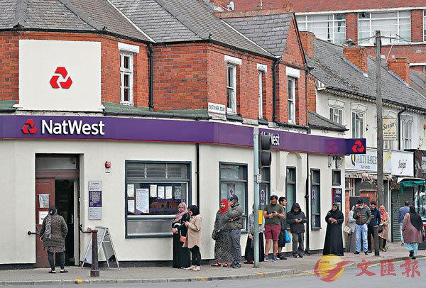 萊斯特不少民眾在封鎖前到銀行,排隊時遵守社交距離。 彭博社