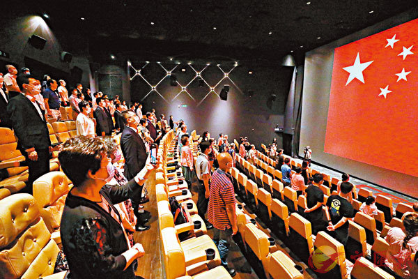 ■放映會舉行前,場內奏響國歌,電影屏幕映出巨幅五星紅旗,全場觀眾肅立面向國旗,隨音樂放聲歌唱。 香港文匯報記者  攝