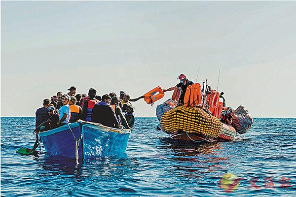 ■ 人道救援人員向難民送上救生衣。 美聯社