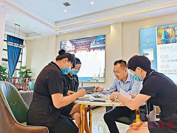 ■陳振輝與同事一起交流工作。 受訪者供圖