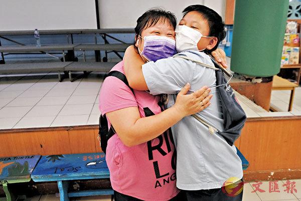 ■陳致勇收到派位證後與母親欣喜相擁。香港文匯報記者  攝