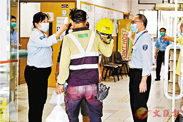 ■地盤工人進入油麻地梁顯利社區會堂開餐前量度體溫。
