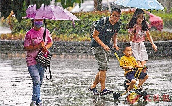 ■8月1日,海口市暴雨傾盆而下,民眾在雨中奔跑尋找避雨處。 中新社