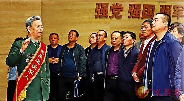 ■ 徐文濤(左一)在東北軍事後勤史館為觀眾講解。 受訪者供圖