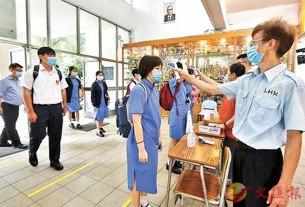 學校於新學年須保持校舍開放,讓家中缺乏親人照顧的學生回校。圖為學校為返校學生測體溫。資料圖片