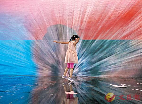 ■一名兒童在服貿會播放宣傳片的大屏幕前。
