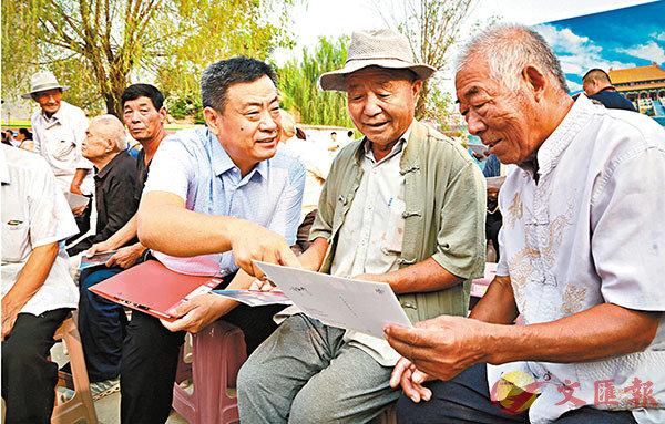 ■ 蘇唐詩(左)向村民介紹自己的攝影作品。