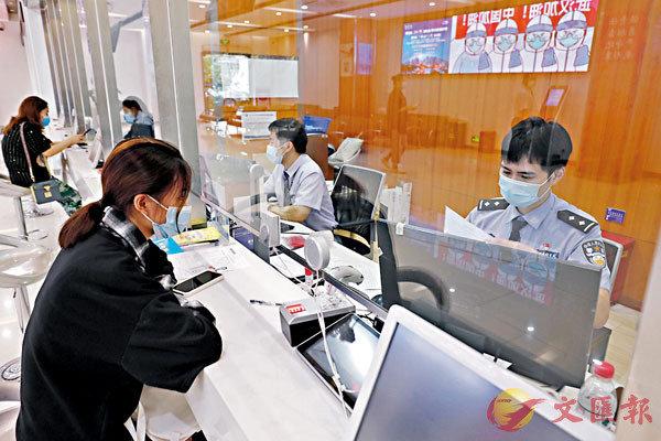 ■ 內地恢復辦理赴澳門旅遊簽註。圖為昨日在上海市公安局長寧分局出入境接待大廳,市民在窗口確認登記信息。 中新社