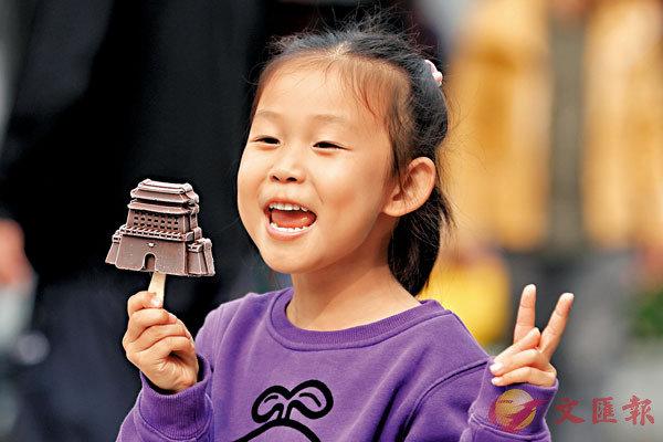 中秋國慶假期中,位於北京前門商業街的「天街冰冰」推出的「前門樓子」冰棍(港稱雪條)受到遊客追捧。圖為10月8日,小朋友手舉「前門樓子」文創冰棍。 文/圖:中新社