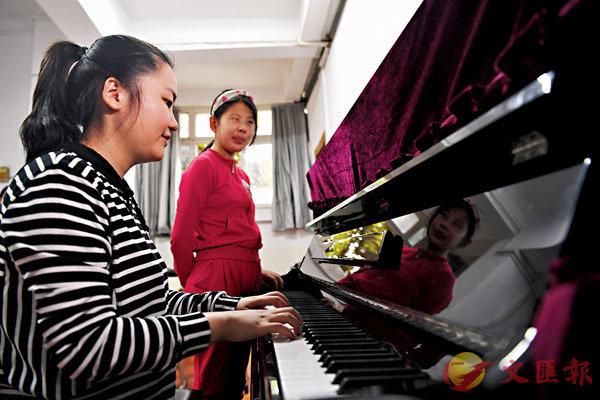 ■王香君(左)在合肥特殊教育中心教視障兒童練習鋼琴。