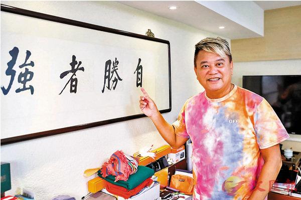 ■陳百祥展示這幅「自勝者強」的書法。 中通社