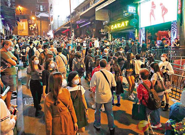 ■大批巿民昨晚湧到中環蘭桂坊慶祝一年一度的萬聖夜,人群雖未如以往般擁擠,但仍十分熱鬧。 香港文匯報記者  攝