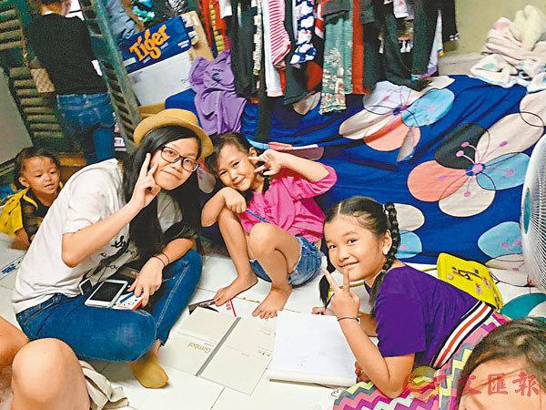 柯嘉瑩曾去柬埔寨義教,為當地兒童分發物資。圖為她與柬埔寨小朋友的合照。受訪者供圖