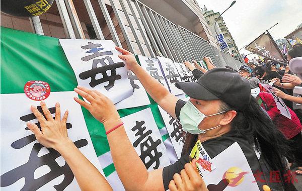 ● 反萊豬吸引數萬台灣民眾上街遊行。圖為民眾在民進黨黨部外的鐵柵欄上張貼標語。 資料圖片
