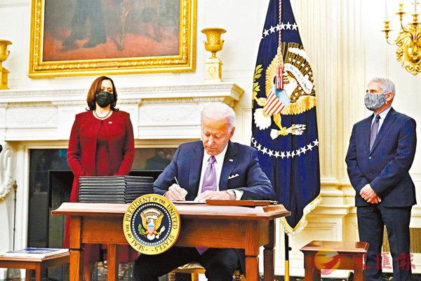 ● 拜登簽署有關抗疫的行政命令,福奇(右)站在他的身後。 美聯社