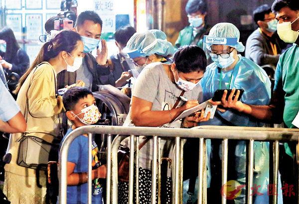 ●東發大廈居民入夜後陸續登記採樣。 香港文匯報記者 攝