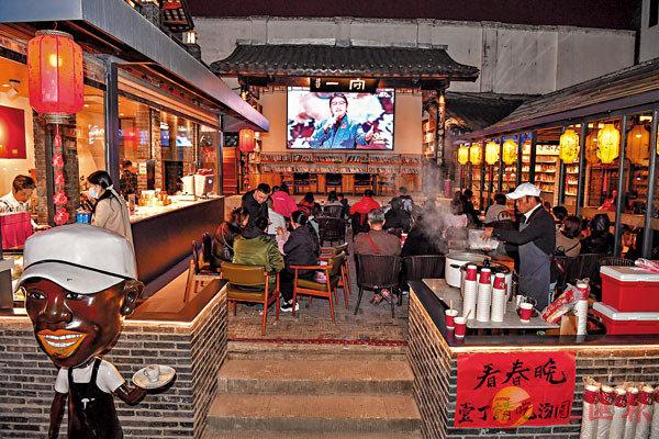 ●市民、遊客在成都寬窄巷子的某咖啡館�堿搰K晚過除夕。 新華社