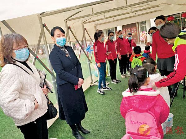 ●上海的一家幼兒園門口,學生們在排隊測體溫。 受訪者供圖