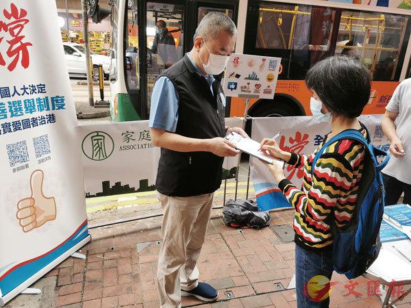 ● 施清流(左)街站呼籲市民簽名支持全國人大關於完善香港選舉制度的決定。
