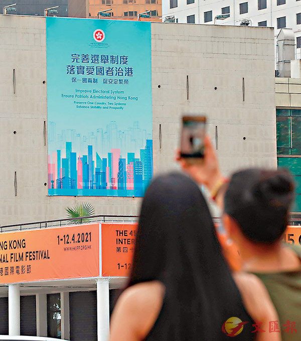 ● 市民用手機拍攝「完善選舉制度」宣傳海報。資料圖片