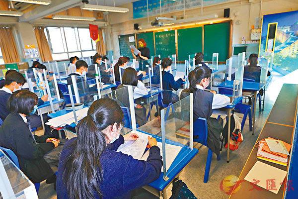 ●5月24日起恢復全校半日面授課堂。圖為早前復課時,學校為每位同學座位設有透明隔板。 資料圖片