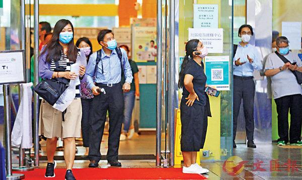 ●昨日本港懸掛一號風球,橫風橫雨無阻巿民到接種站打疫苗。 香港文匯報記者  攝