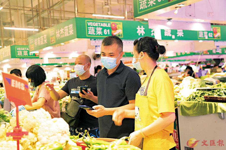 ● 祈福新村社區市場物資充足,黃繼堅採購食物回家過節。 香港文匯報記者胡若璋  攝
